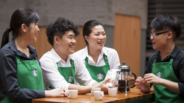 Four smiling baristas stand together